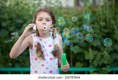 Portrait of little girl blowing soap bubbles