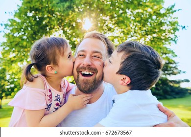 Portrait of little girl and boy embracing and kissing their bearded father outdoors in summer