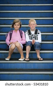 Portrait of a little girl and a little boy sitting on the steps of stairs