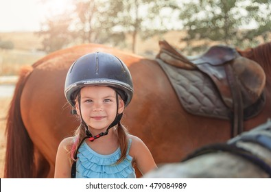 Portrait of little girl and brown Horse. Girl with Helmets for Equestrian.