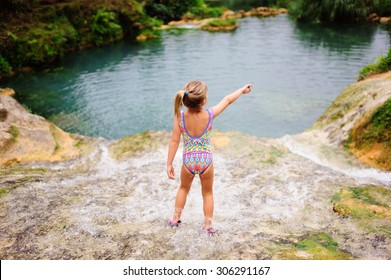 A portrait of a little girl at the cascades of Vanuatu wearing a colourful swimming suit standing with her back to the camera and pointing to something in front of her