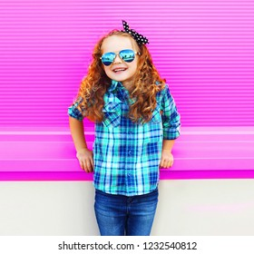 Portrait little girl child in checkered shirt, sunglasses on colorful pink wall background