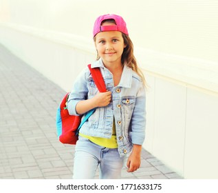 Portrait of little girl child wearing a baseball cap with backpack on background