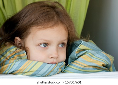 portrait of a little girl covered by blanket in the open window