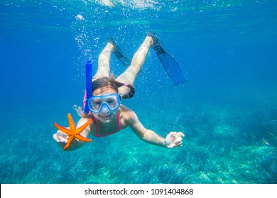 portrait of a little girl diving the sea for a starfish