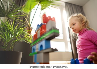 portrait of a little girl with a dog in the interior plays a constructor on the background of a window and sunbeams