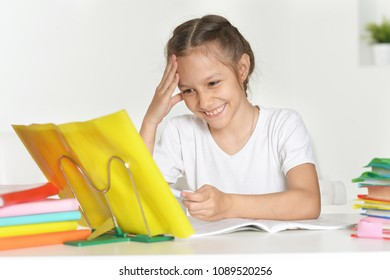 portrait of little girl doing lessons at table