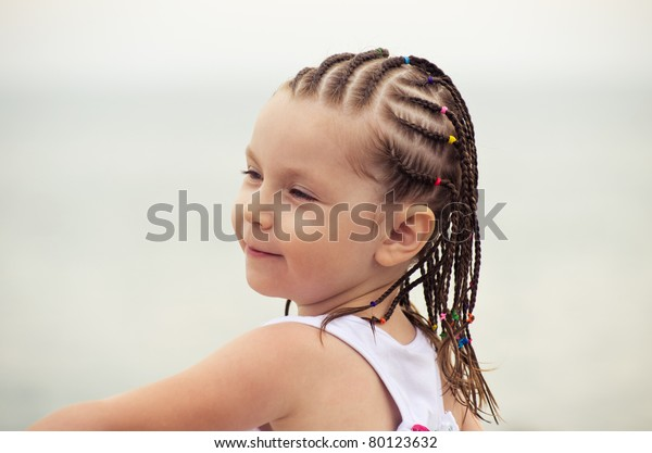Portrait of little girl with dreadlocks on the beach