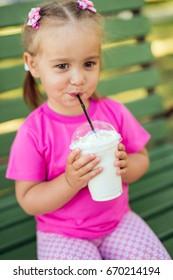 Portrait of little girl drinking fresh milkshake in the park