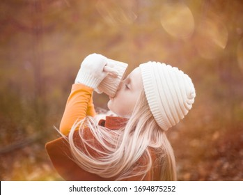 Portrait of little girl drinking tea outdoors in autumn. Cute child wearing knitted hat holding cup. Childhood, season, hot drink