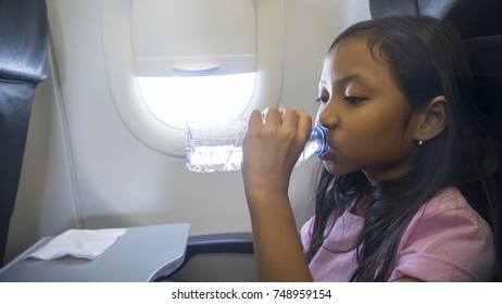 Portrait of a little girl drinking water with a bottle in the airplane