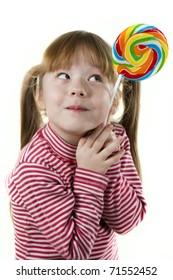 portrait of a little girl eating a lollipop
