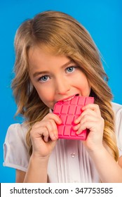Portrait of a little girl eating pink chocolate isolated on blue background