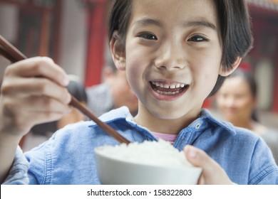 Portrait of little girl eating rice