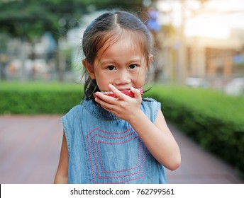 Portrait of little girl eating sliced dragon fruit