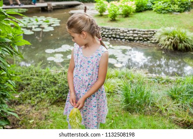 Portrait of little girl in elegant dress at nature, beautiful spring day at park