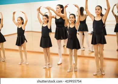 Portrait of a little girl enjoying her ballet class with a group of girls and a dance teacher