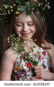 portrait of little girl with flowers on head in Studio on dark background vertical