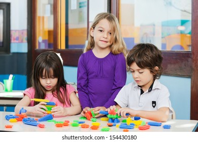 Portrait of little girl with friends playing blocks in kindergarten
