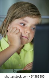 Portrait of a little girl in front a laptop computer
