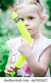 Portrait of a little girl. Funny 3 year old. Girl on picnic nature. Cute little girl. Summer Games, Playing outdoors. Girl and Boomerang