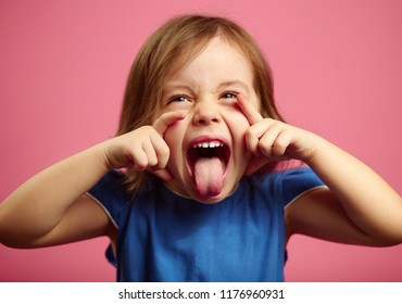 Portrait of little girl grimace and shows tongue on pink isolated