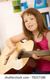 Portrait of little girl with guitar, looking at camera, smiling.