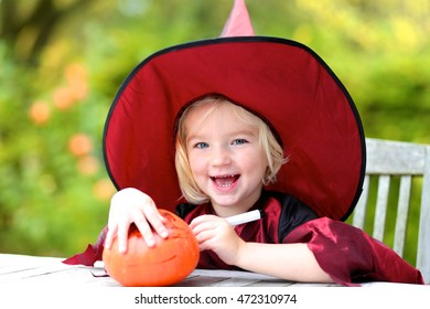 Portrait of little girl in Halloween witch costume decorating pumpkin outdoors in the garden. Kraft for kids.