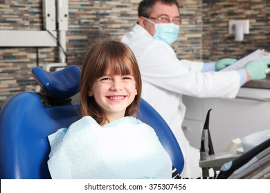 Portrait of little girl has a dental examination. Male dentist and his smiling child patient sitting at dentist office.