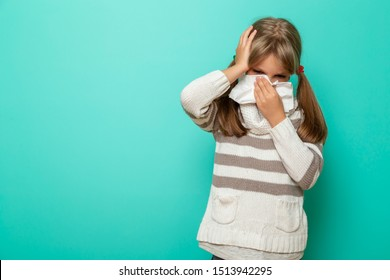 Portrait of a little girl having a flu, fever and headache, blowing and wiping nose with paper tissues