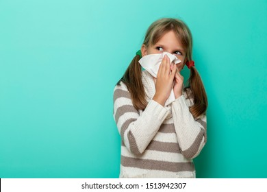Portrait of a little girl having a flu, blowing and wiping nose with paper tissues on mint colored background