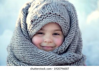 Portrait of a little girl in a headscarf in winter.
