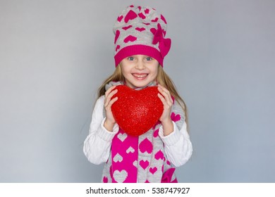 portrait of a little girl with a heart in the hands of the holiday Valentine's Day