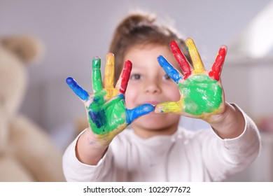 Portrait of a little girl in her bedroom showing her hands all colored with paint. Concept of: color, creativity, art, happiness and educational.