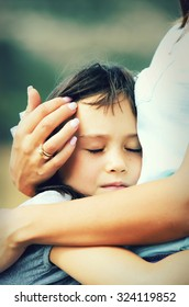 Portrait of a little girl with her eyes closed  hugging mother, outdoor