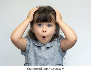 Portrait of little girl holding hands on head, screaming with opened mouth and crazy expression. Surprised or shocked face