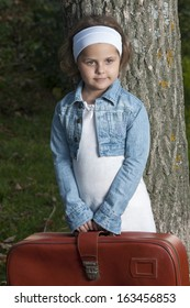 Portrait of little girl holding old traveling bag