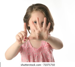 Portrait of a little girl holding up six fingers in front of her face to show hold old she is, isolated on white