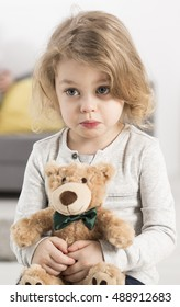 Portrait of a little girl holding a teddy bear in her hands