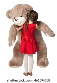 Portrait of a little girl hugging a big teddy bear toy, view from the back, isolated on white background