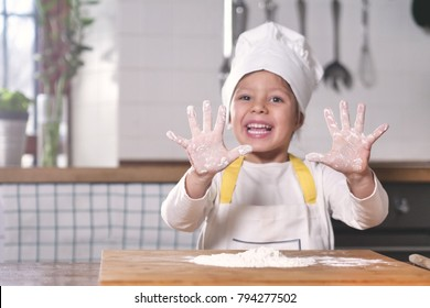 Portrait of a little girl in the kitchen dressed as a professional cook playing with flour, gets her hands dirty and smiles happy. Concept of: nutrition, cooking school, education and game.