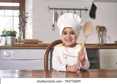 Portrait of a little girl in the kitchen dressed as a professional cook smiling and holding a traditional wooden kitchen spoon in her hand. Concept of: nutrition, cooking school, education and family.