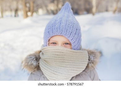 Portrait of little girl in knitted hat and scarf in winter
