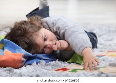 Portrait of a Little girl laid on a carpet