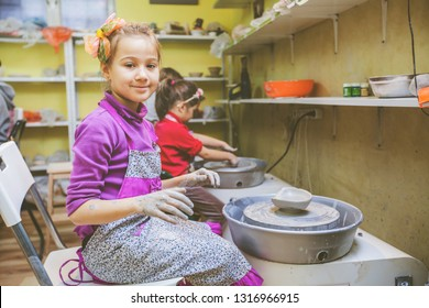 Portrait of little girl learning new skill at pottery workshop .