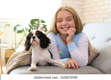 Portrait of little girl with long blonde straight hair playing with black and white Cavalier King Charles Spaniel puppy at home. Child with her pet friend. Lofty interior design. Close up, copy space.