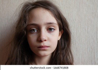 Portrait of a little girl with long flowing hair on a light background