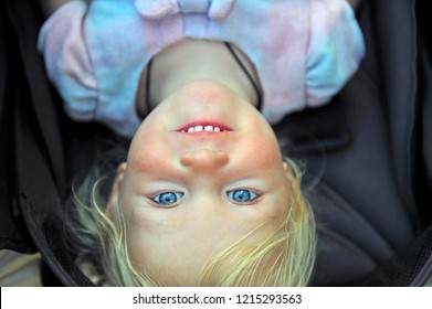 Portrait of a little girl looking at camera upside down