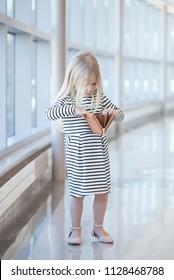 Portrait of little girl looking into empty wallet in mall