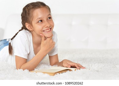 portrait of a little girl lying on the bed and reading a book